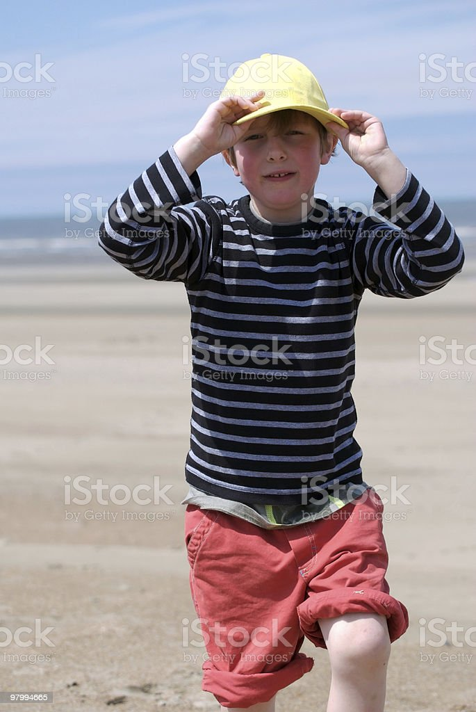 Running boy with a yellow cap, beach, summer vacation royalty-free stock photo