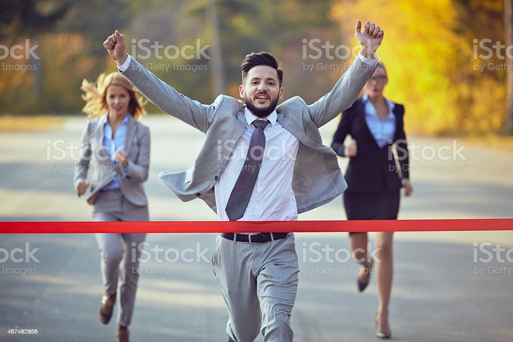 Running businessman about to cross a red finish line stock photo