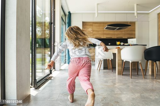 Long haired girl in pajama running in the kitchen at home