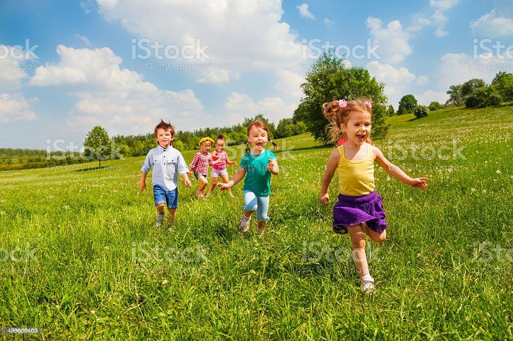 Running children in green field during summer stock photo
