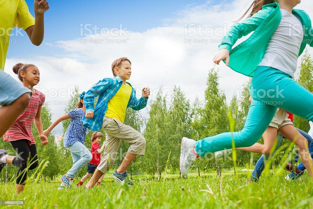 Running children view in the green field stock photo