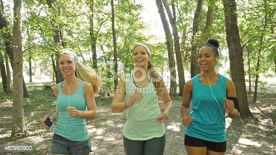 1051098428 istock photo Running club exercising together on dirt trail in park 482983902