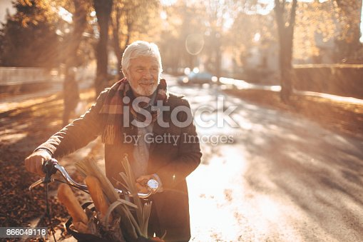 Photo of a fashionable senior man, running his errands on a bicycle