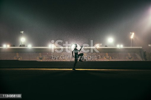 Silhouette side view of a young muscular Caucasian male exercising running warming up in the rain at night in the dark in front of a stadium with stadium floodlights spotlights near Cape Town South Africa