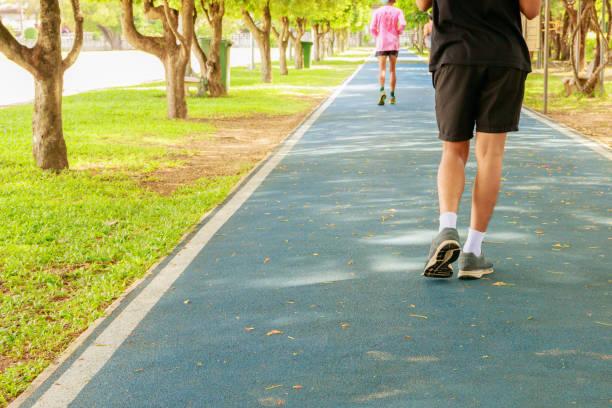 laufende füße männlichen im läufer joggen übung mit alten schuhen für gesundheit verlieren gewichtskonzept auf track kautschuk abdeckung blau volkspark. textfreiraum text hinzufügen - gewicht schnell verlieren stock-fotos und bilder