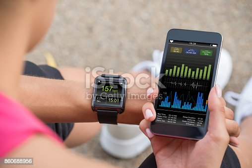 istock Running Female With Mobile Phone Connected To A Smart Watch 860688956