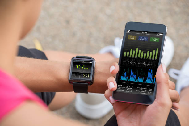 running female with mobile phone connected to a smart watch - sports medicine stock photos and pictures