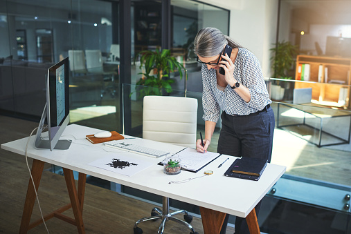 Shot of a confident mature psychologist using a smartphone and making notes in a modern office