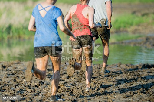 687723318istockphoto Running in a Mud Run 687722912