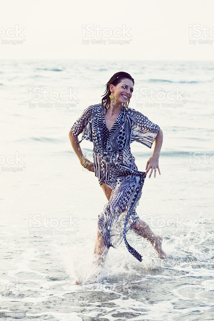 Running in a ocean Summer vacation. Happy woman wearing summer dress running in water. 25-29 Years Stock Photo