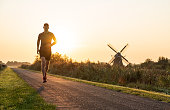 Man running in the Dutch countryside near a traditional windmill. Groningen, Holland.