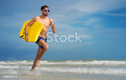 Running in the beach holding a yellow skimboard Florida