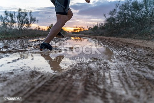 986840244 istock photo Running in the field at sunset in shorts, with sneakers, along a path with puddles that reflect the sunset. 1079985062