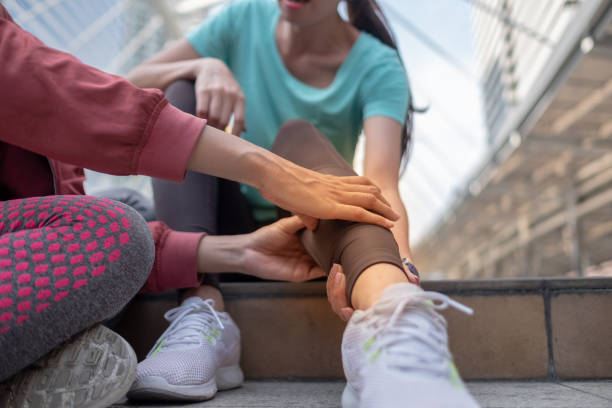 running injury leg accident- sport woman runner hurting holding painful sprained ankle in pain, someone help to first aid before move to hospital. - caviglia foto e immagini stock