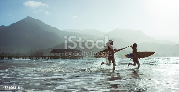 Three people on a beach, running into the ocean with surfboards in a tropical climate, with mountains in the background.