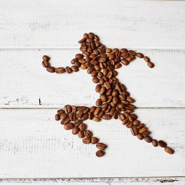 A running man assembled from roasted coffee beans on a white wooden surface A running man assembled from roasted coffee beans on a white wooden surface caffeine stock pictures, royalty-free photos & images