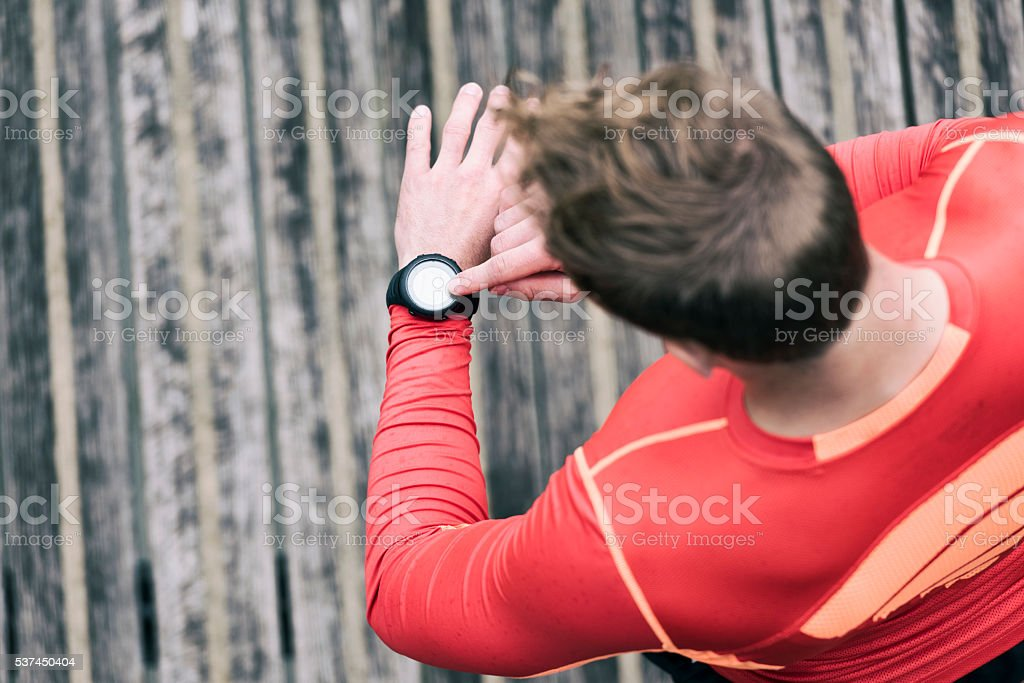 Running man looking sportwatch. Male jogging using smart watch o royalty-free stock photo