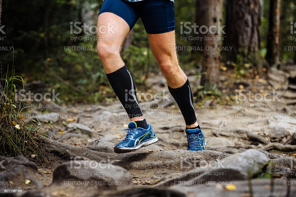 running marathon runner in woods over rocks stock photo