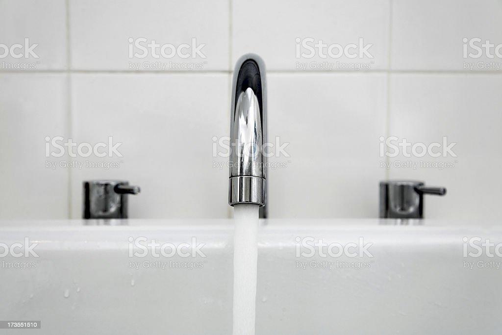 Running Mixer Tap in White Enamel Bath stock photo
