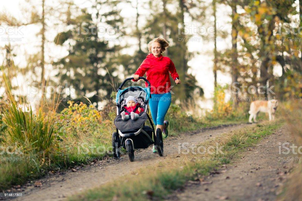 Laufende Mutter mit Kinderwagen Mutterschaft im Herbst Sonnenuntergang genießen – Foto