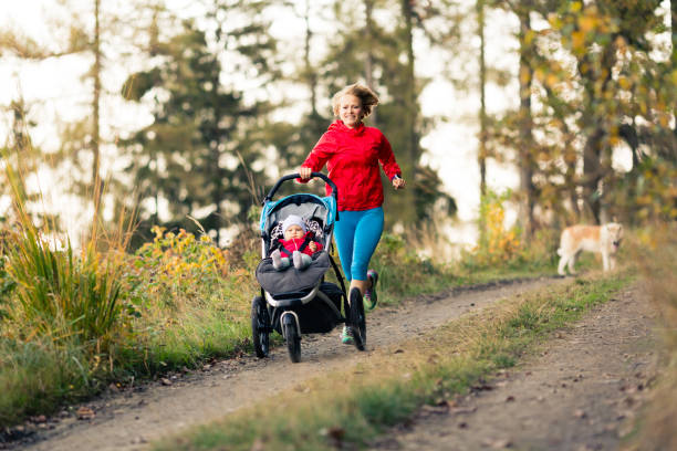 Running mother with stroller enjoying motherhood at autumn sunset stock photo