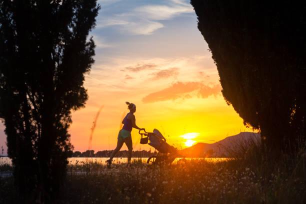 L'exécution de mère avec poussette, profitant de la maternité au paysage coucher de soleil - Photo