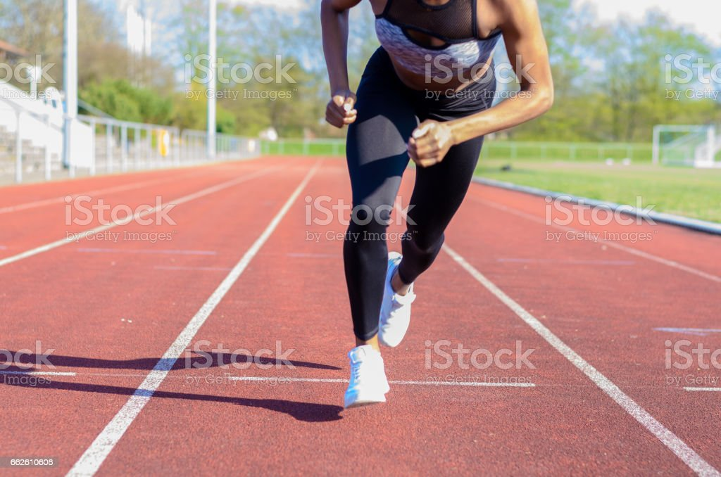 Running muscular legs of a young athlete stock photo