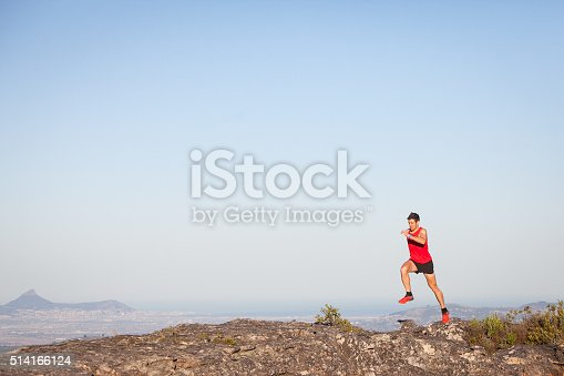 Male in a red top enjoys a fast paced run on top of a mountain