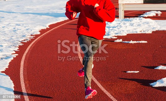 986840244istockphoto Running on a track with snow 977491064