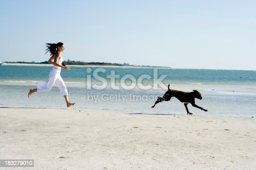 Young attractive woman running her healthy boxer.