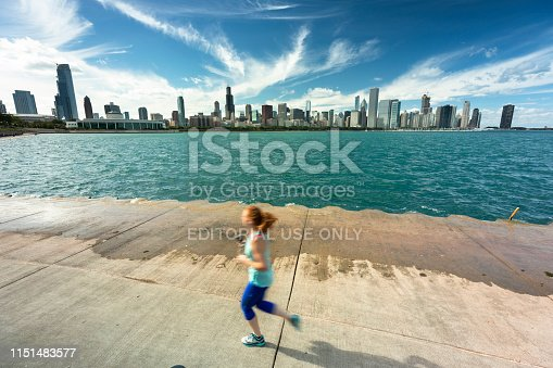Chicago, Illinois, USA - September 21, 2018:  A young woman runs on the Lakefront Trail on Lake Michigan in Chicago Illinois USA.