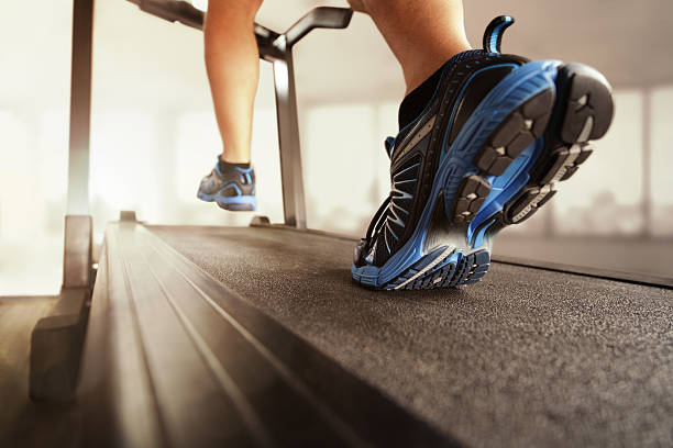 Running on treadmill Man running in a gym on a treadmill concept for exercising, fitness and healthy lifestyle treadmill stock pictures, royalty-free photos & images