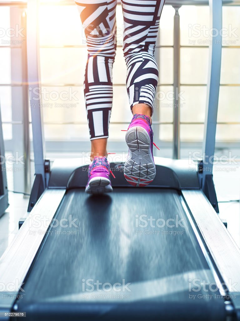 Running on treadmill Woman walking on treadmill. Morning training at sunrise Active Lifestyle Stock Photo