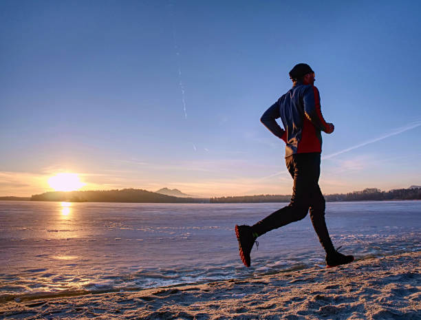 Running or jogging on beach in winter, sunny day morning stock photo