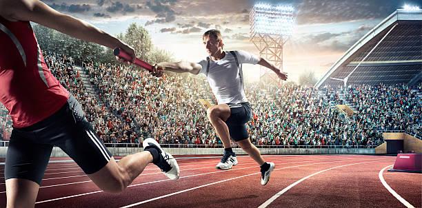 running fahren sie auf dem olympic stadium - staffelstab stock-fotos und bilder