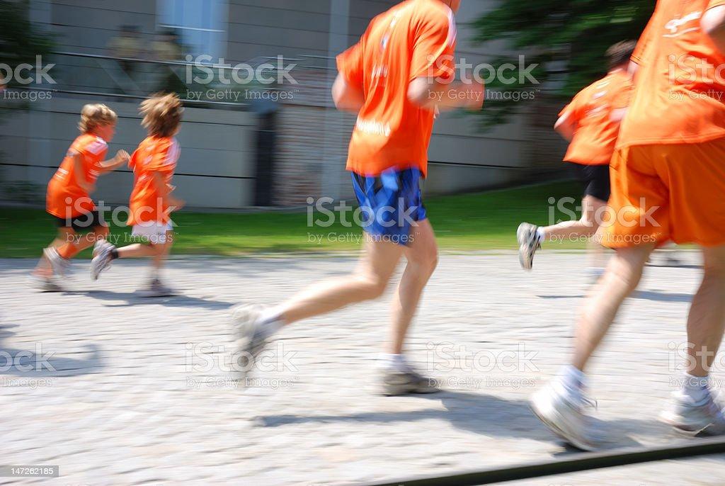 running people in orange shirts, motion blur royalty-free stock photo