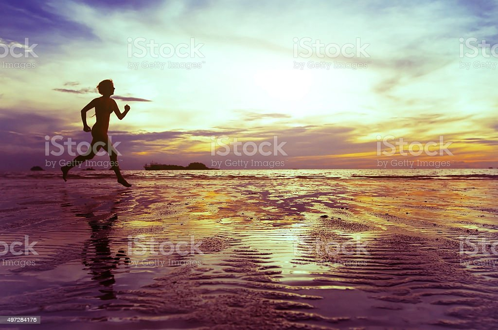 running person on the beach stock photo
