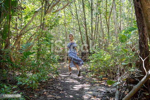 A young woman in a beautiful blue dress playfully runs down a wilderness trail in Fort Lauderdale, Florida.