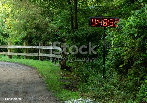 A clock is nine minutes into a 10K running race being held in the woods on a dirt trail souranded by trees.