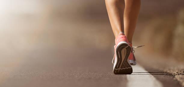 running shoe closeup of woman running on road - stopa zdjęcia i obrazy z banku zdjęć