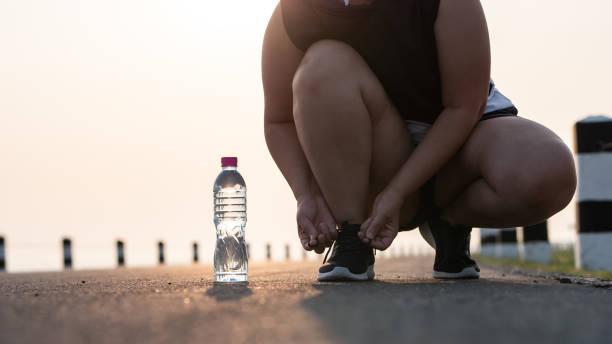Zapatos de Running-cierre de mujer atar cordones de zapatos. Ella se está preparando para correr en la luz del sol de la madrugada. concepto de perder peso con el ejercicio. con el espacio de copia. - foto de stock
