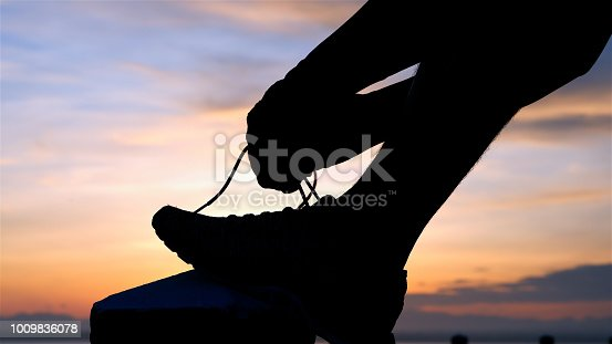 Running shoes - Man is tying shoe laces. male sport fitness runner getting ready for jogging outdoors the time during sunrise on dam road exercise.