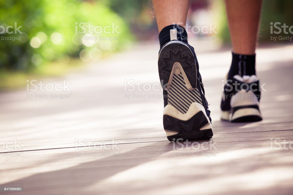 Running Shoes of Man Walking in the Park stock photo