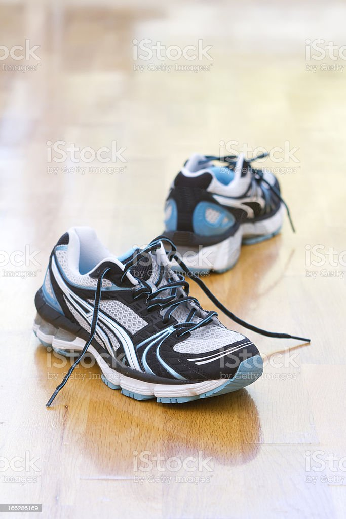 Running shoes on a wooden gym floor royalty-free stock photo