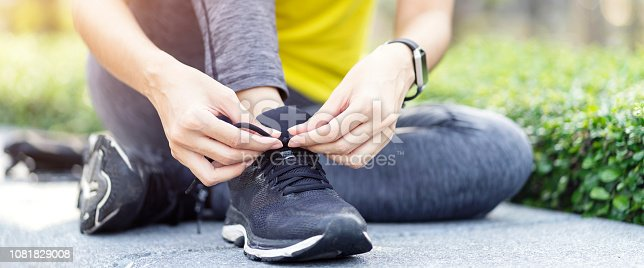 istock Running shoes - Woman tying shoelaces, Sporty fitness runner getting ready for jogging at garden. Horizontal photo banner background. 1081829008