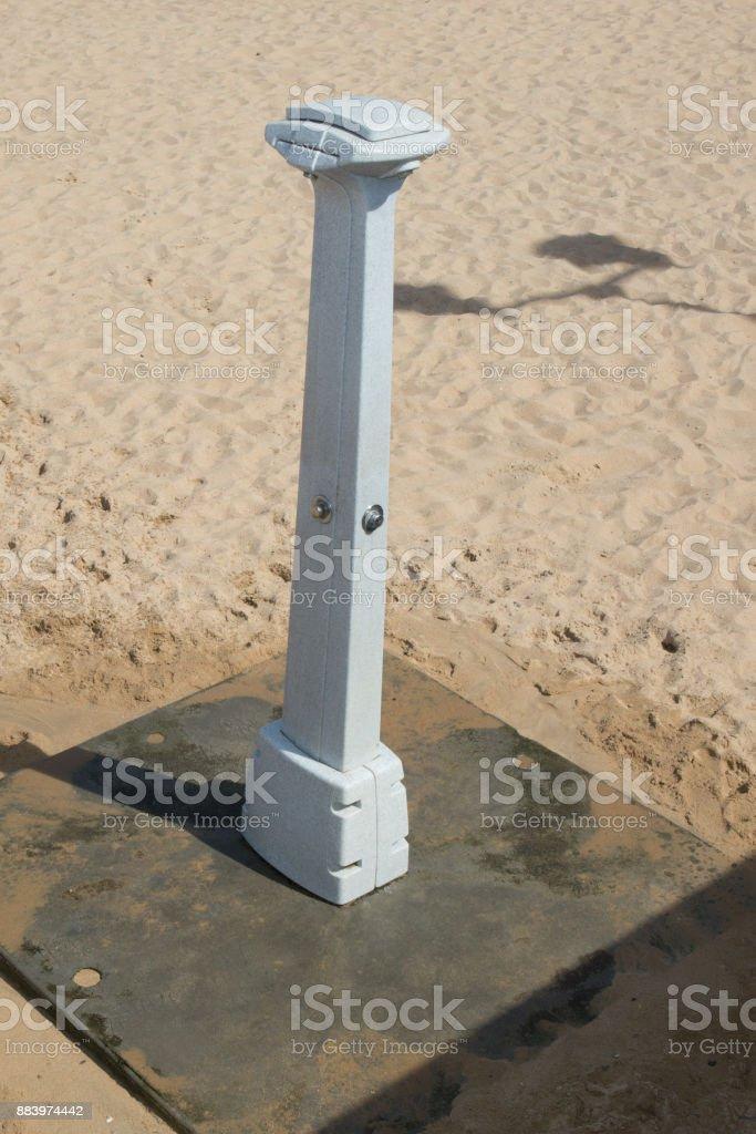 Running shower on the beach, under blue sky stock photo