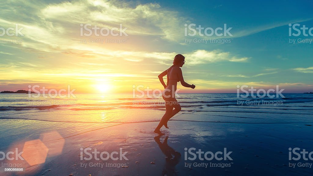 Running silhouette of young girl on the sea beach royalty-free stock photo