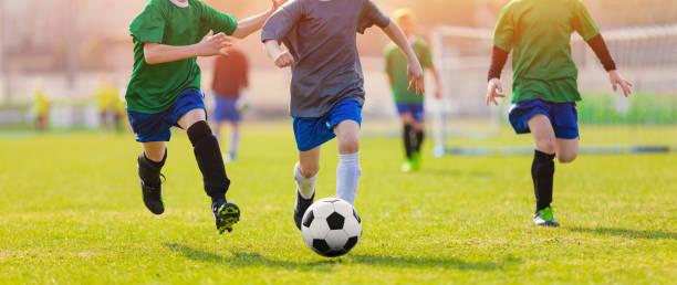 fussball spieler während des sonnenaufgangs. fußballer kicking football match. fußballschulturnier. junge fußball-spieler laufen nach dem ball fußballstadion im hintergrund - fußball wettbewerb stock-fotos und bilder