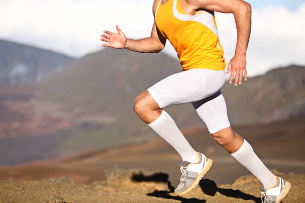Running sport fitness man - closeup Running sport fitness man. Closeup of strong legs and shoes in action. Male athlete fitness runner sprinting fast outside in compression sports clothing, socks and tights shorts. Trail running concept shorts stock pictures, royalty-free photos & images