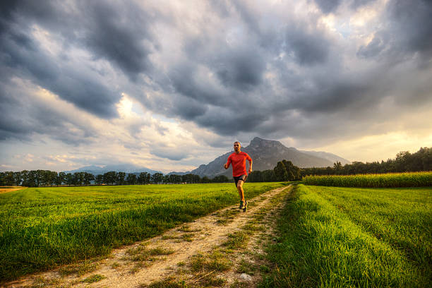 Running Through Alpine Valley Muscular young man running through the valley with tall mountains and sunset lit clouds behind him.   davelongmedia stock pictures, royalty-free photos & images